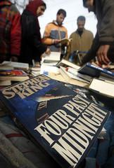 Kashmiris browse through second-hand books at a vendor's stall in Srinagar