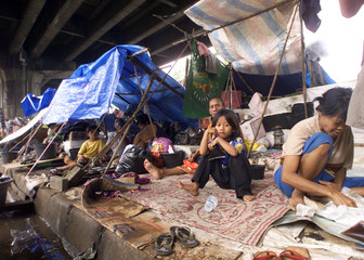 INDONESIAN RESIDENTS TAKE SHELTER UNDER A FLY OVER IN JAKARTA.