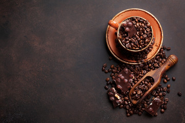 Coffee cup with roasted beans and chocolate