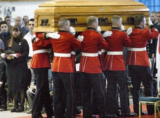 CASKET OF CANADIAN SOLDIER IS CARRIED PAST HIS WIFE AT FUNERAL.