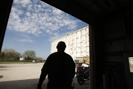 A worker walks near elevators with wheat and corn in Lincoln, Nebraska