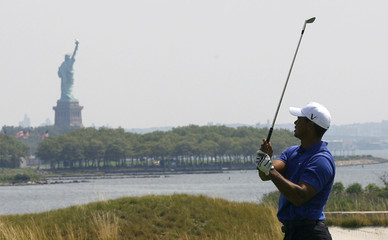 New York's Statue of Liberty is seen in the background as Tiger Woods from the U.S. hits on the 18th hole