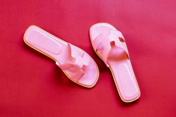 Pink sandals on Red background top view with copy space