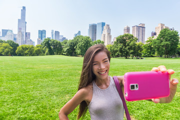 Wall Mural - Happy Asian woman taking smartphone selfie photo with mobile phone at sheep meadow, Central park. Girl tourist enjoying american summer travel vacation in New York City, Manhattan, USA.