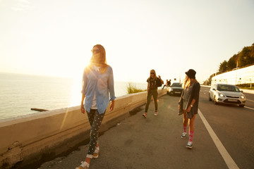 Girls travelers walking down the roadside on the sea coast on the sunset