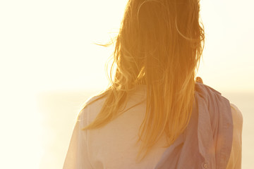 Girl's hair waving on the sunset from back side