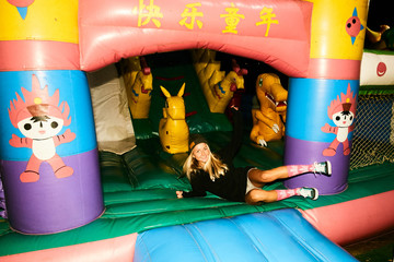 Girls fooling around in an inflatable trampoline like children