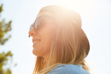Portrait of a girl in the sun smiling and wearing sunglasses