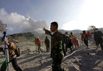 Soldier asks journalists and rescue team members to leave bunker after Mount Merapi volcano starts spewing thick smoke again in Kaliadem