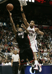 Miami Heat guard Chalmers shoots under basket past Atlanta Hawks center Horford in first round of the NBA Eastern Conference basketball playoffs in Atlanta