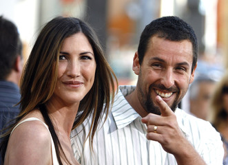 Adam Sandler gestures next to his wife Jackie at the premiere of I Now Pronounce You Chuck and Larry at the Gibson amphitheater in Universal City