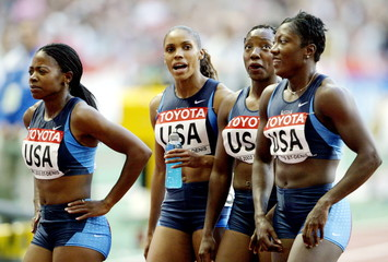 The U.S. 4x100 metres women's team stand dejected after the women's 4x100 metres relay final during ..