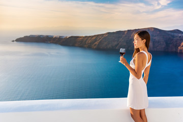 Fototapete - Luxury hotel terrace. Europe destination summer vacation. Asian woman drinking red wine relaxing enjoying view of the mediterranean sea in Oia, Santorini, Greece. Honeymoon high end travel holiday.