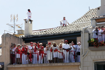 People watch revellers from a balcony at the start of the San Fermin festival in Pamplona