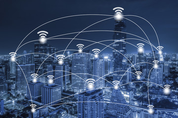 Wifi network connection concept on blue tone aerial view of cityscape business district at twilight background.