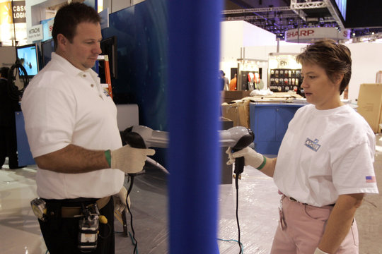 David Olszens and Pamela Harrison use hair dryers to take wrinkles out of both sides of a projection screen in the Blu-ray booth at the 2007 International CES in Las Vegas