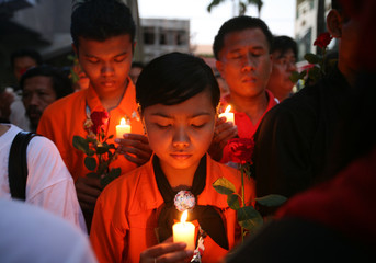 People attend a candlelight vigil outside a restaurant which was bombed in Bali
