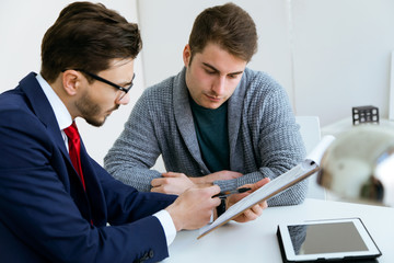 Business young man explaining terms of contract to his client in the office.
