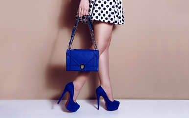 Slim woman wear skirt legs in high heels shoes with blue bag