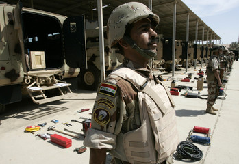 Iraqi soldiers stand next to new equipment and Badger armoured vehicles at Taji military base in Baghdad