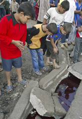 Children look at bloodied water in a ditch after a joint Iraqi and U.S. forces raid in Baghdad's Sadr city