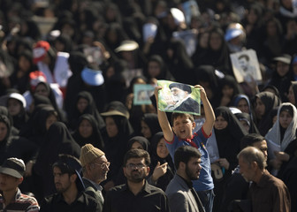 A boy holds a picture of supreme leader Khamenei during a ceremony south of Tehran