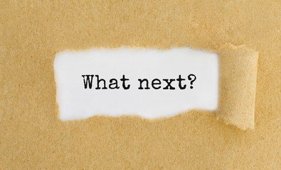 Text What next appearing behind ripped brown paper