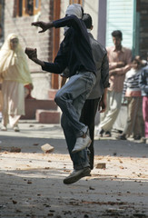 A masked Kashmiri protester throws a brick at Indian policemen during a protest in Srinagar