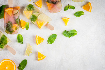 Homemade ice cream. Frozen drinks. Fresh fruits, citrus. Popsicles of red, white sangria, lemonade or mojito. With oranges, lime, mint, apples. White stone table, ingredients. Copy space