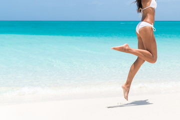 Beach ready sexy bikini body - lean legs, thighs and butt. Suntan happy woman jumping in freedom barefoot on white sand. Weight loss success or epilation concept. Copy space on ocean background.