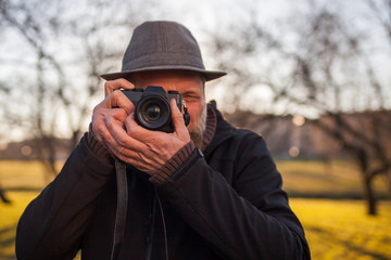 A mature man in a hat takes pictures on a mirrorless camera in the street. Hobby of photography. New trends in photographic technique.