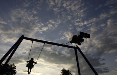 Children play on swings in Langen near Frankfurt