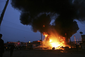 Firemen try to extinguish a fire at a petrol station after a bomb attack in Baghdad