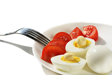 Chicken boiled eggs on a white plate with slices of red tomato on a white background