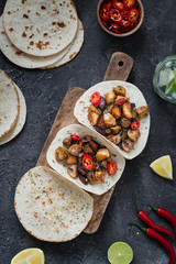 Tacos with grilled mushrooms, Spanish spicy sausage chorizo, Mexican tortillas, Cypriot cheese halloumi, hot chilly, dried oregano and glass of water with lime, top view on dark rustic background