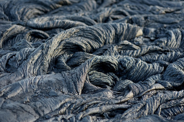 Smooth, undulating surface of frozen pahoehoe lava. Frozen lava wrinkled in tapestry-like folds and rolls resembling twisted rope on Big Island of Hawaii