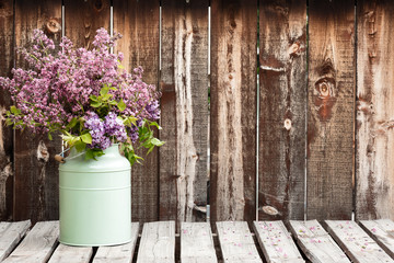 Large bouquet of lilacs in a green container on a rustic wooden table. Wall mural
