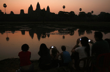 Tourists take photos of the sunrise over Angkor Wat in Siem Reap