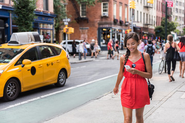 Woman walking in new york city using phone app for taxi ride hailing service or playing online game...