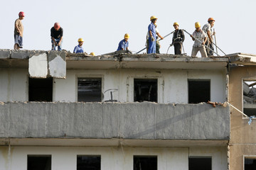 Workers demolish old residential building to construct new commercial structure in Beijing