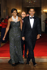 U.S. President Barack Obama and first lady Michelle Obama enter the East Room to hear Earth Wind and Fire perform at the Governors dinner at the White House in Washington