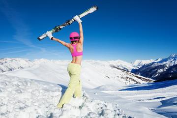 Female skier in sports bra lifting up pair of ski