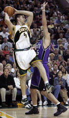 Seattle SuperSonics' Nick Collison looks to make a midair pass while covered by Sacramento Kings' Peja ...