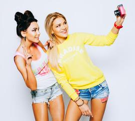 Two girls taking self image together on pink vinage camera, indoor.