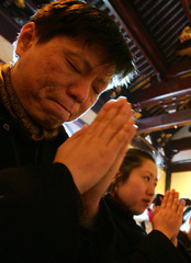 Chinese worshippers pray at a temple to celebrate the Lunar New Year in Shanghai.