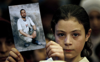A Palestinian girl, who is a Hamas supporter, holds up a picture of a jailed relative during a demonstration in Ramallah