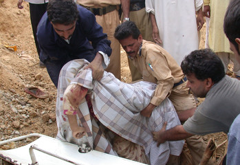 AMBULANCE WORKERS REMOVE A BODY AFTER A MUDSLIDE IN KARACHI.