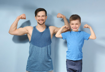 Father and son in sportswear on color background