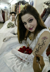 An Iraqi bride-to-be has a decorative flower pattern applied to her arm at a beauty parlour in the c..