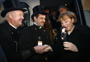German Chancellor Merkel receives a chimney sweeper doll from a group of chimney sweepers during her visit at the 50th anniversary of the southwestern German state of Saarland in Merzig